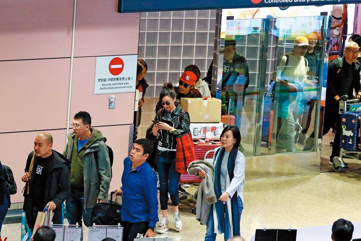 1/20 16:19 本刊直擊張栢芝(中)與經紀人現身桃園機場,相隔不到1週再度來台,張栢芝一路滑手機。