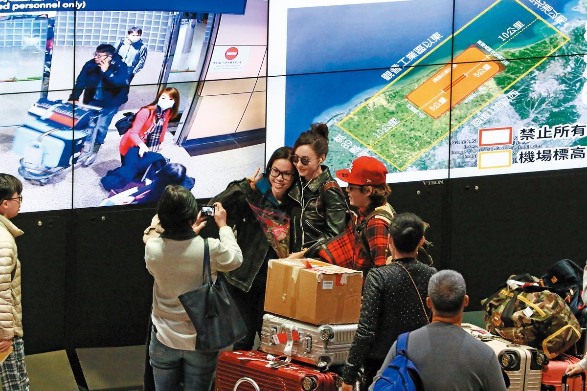1/20 16:20 神通廣大的粉絲到機場迎接張栢芝,她也來者不拒,簽名、合照樣樣來,作足粉絲服務。