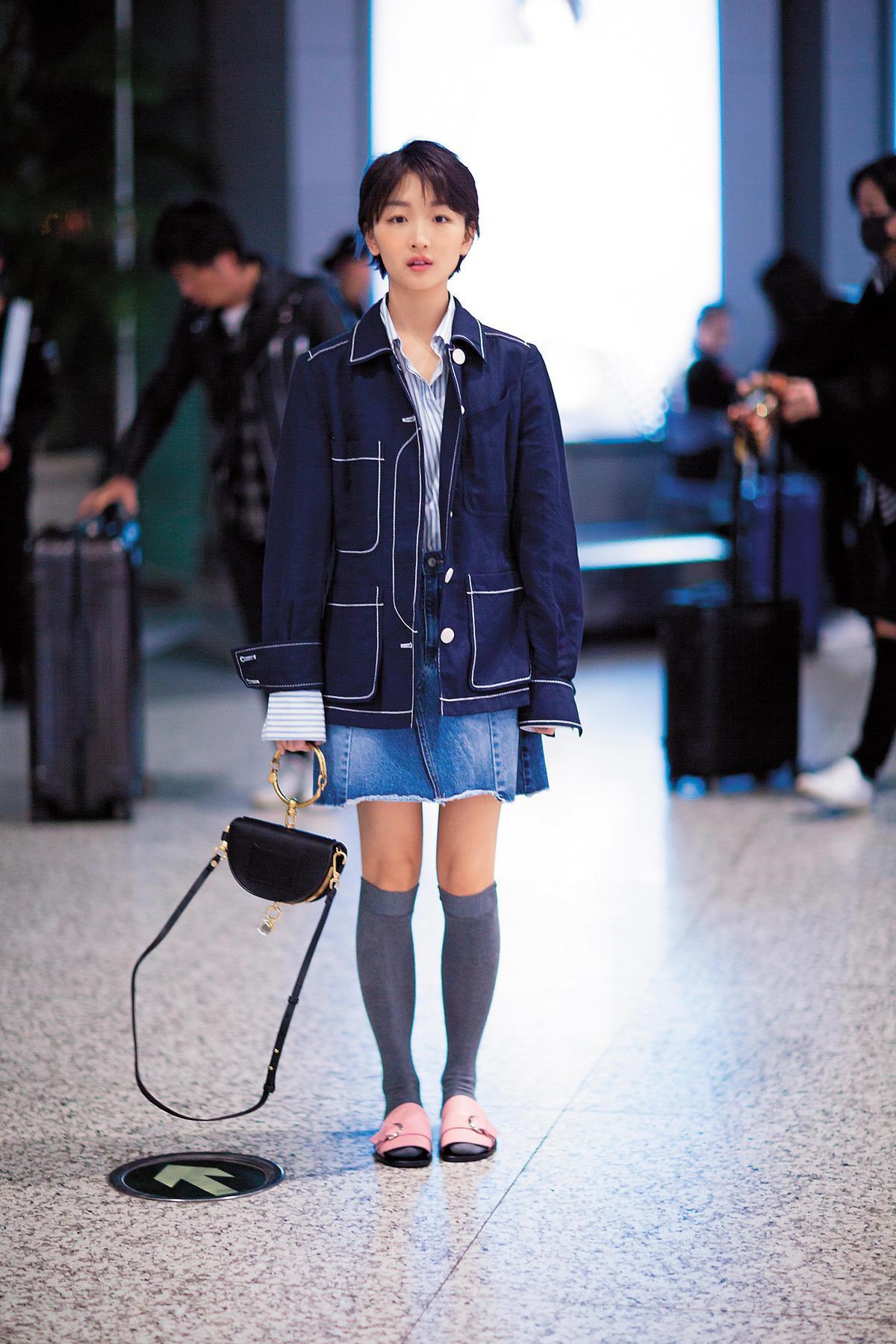 拎著Chloé手袋的周冬雨,以稍微寬鬆的牛仔西裝式外套搭配牛仔短裙,長統襪與粉色拖鞋是另類的學生妹風格,很潮。(東方IC)