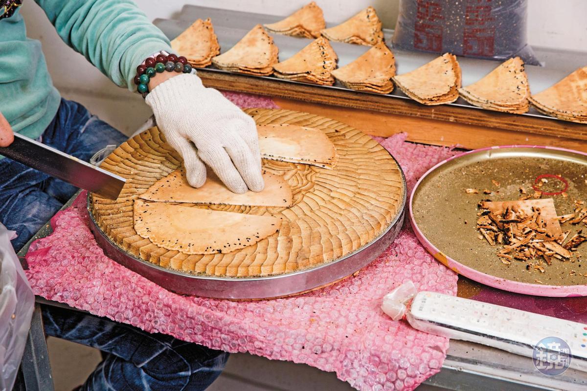 選用竹製砧板分切剛烤好的煎餅,可避免沾黏砧板木屑,再趁餘溫塑形。