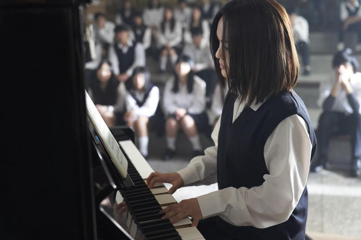 徐佳瑩在禮堂彈鋼琴,一起入鏡的都是貨真價實的高中生。(亞神提供)