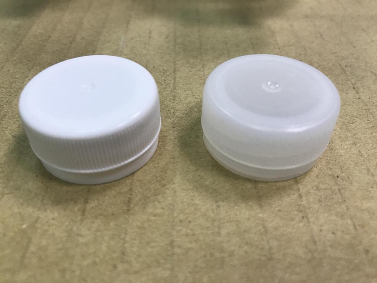 丹楓礦泉水辨識真假(右真左假)業者表示,回收瓶裝水裝填粗糙,光從瓶蓋即可以分辨。(保七總隊提供)