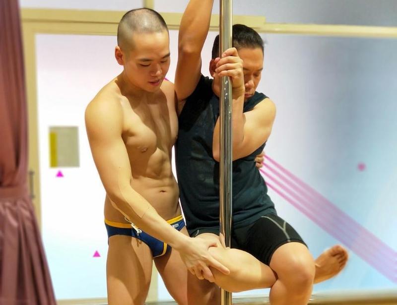 卜學亮為三立《愛台客-在台灣的故事》挑戰鋼管舞,被僅穿三角褲的小鮮肉教練貼身訓練夾鋼管。(三立提供)