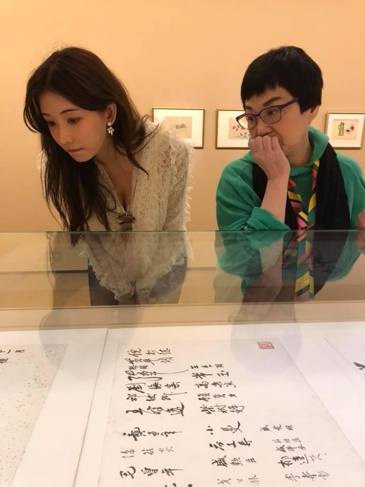 張小燕與林志玲2人仔細端詳展場作品,志玲姐姐忘我不慎露出深溝。(翻攝自蔡康永臉書)