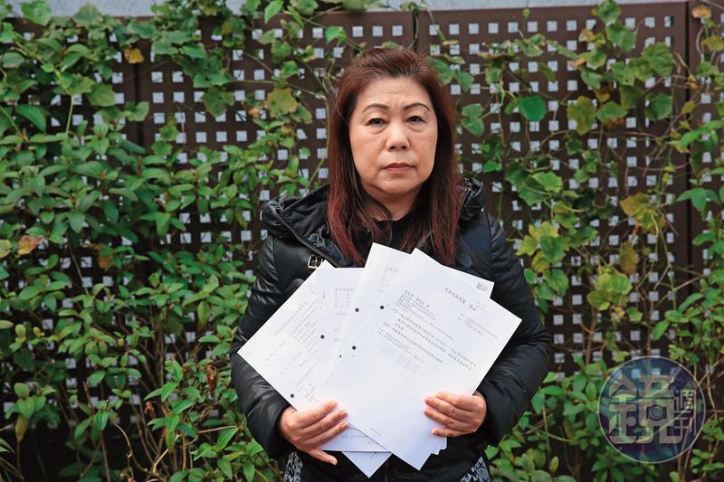 羅女拿著含檢舉函在內的法院文書,控訴司法不公。