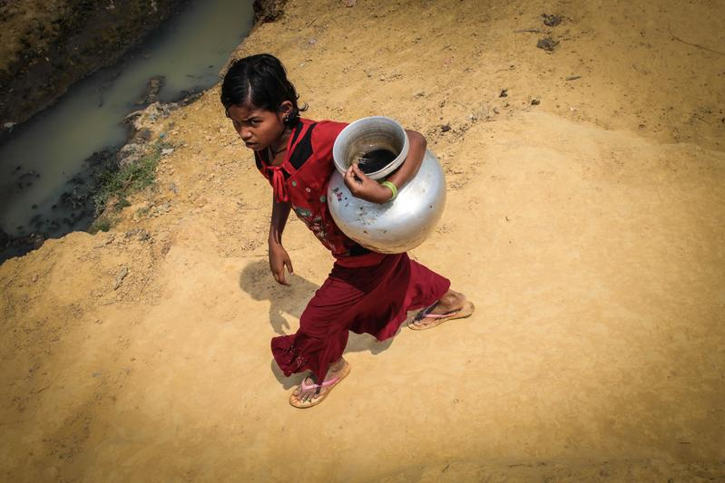 打水後返回難民營的羅興亞女孩。(東方IC)