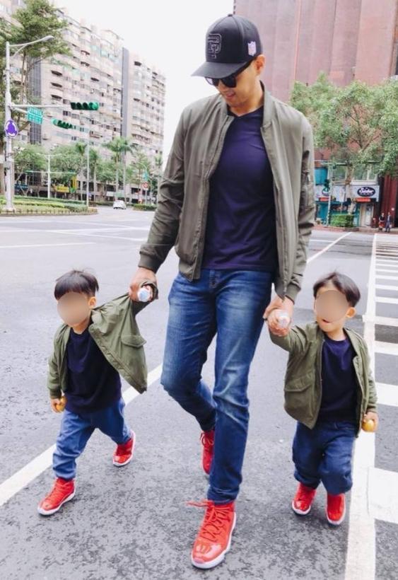 黑人牽雙胞胎兒子拍街拍照片,被網友說違反交通法規。(網路圖片)