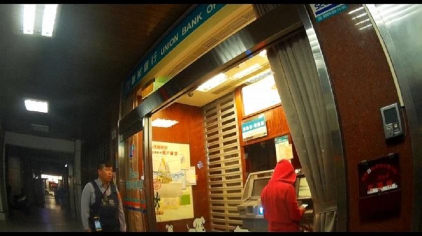 員警簽巡金融機構巡邏箱,站林姓女子身後觀察她領錢。(警方提供)
