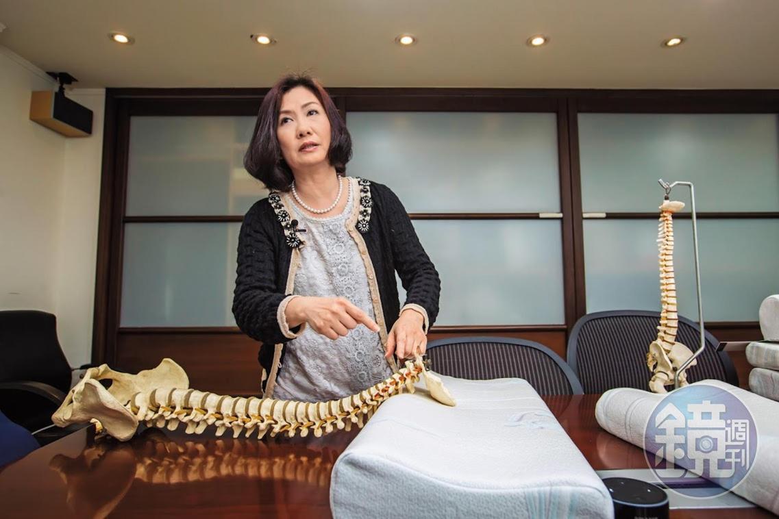 譚芙芩利用人體脊椎模型,在裸枕上調整示範正確頸枕睡眠姿勢。
