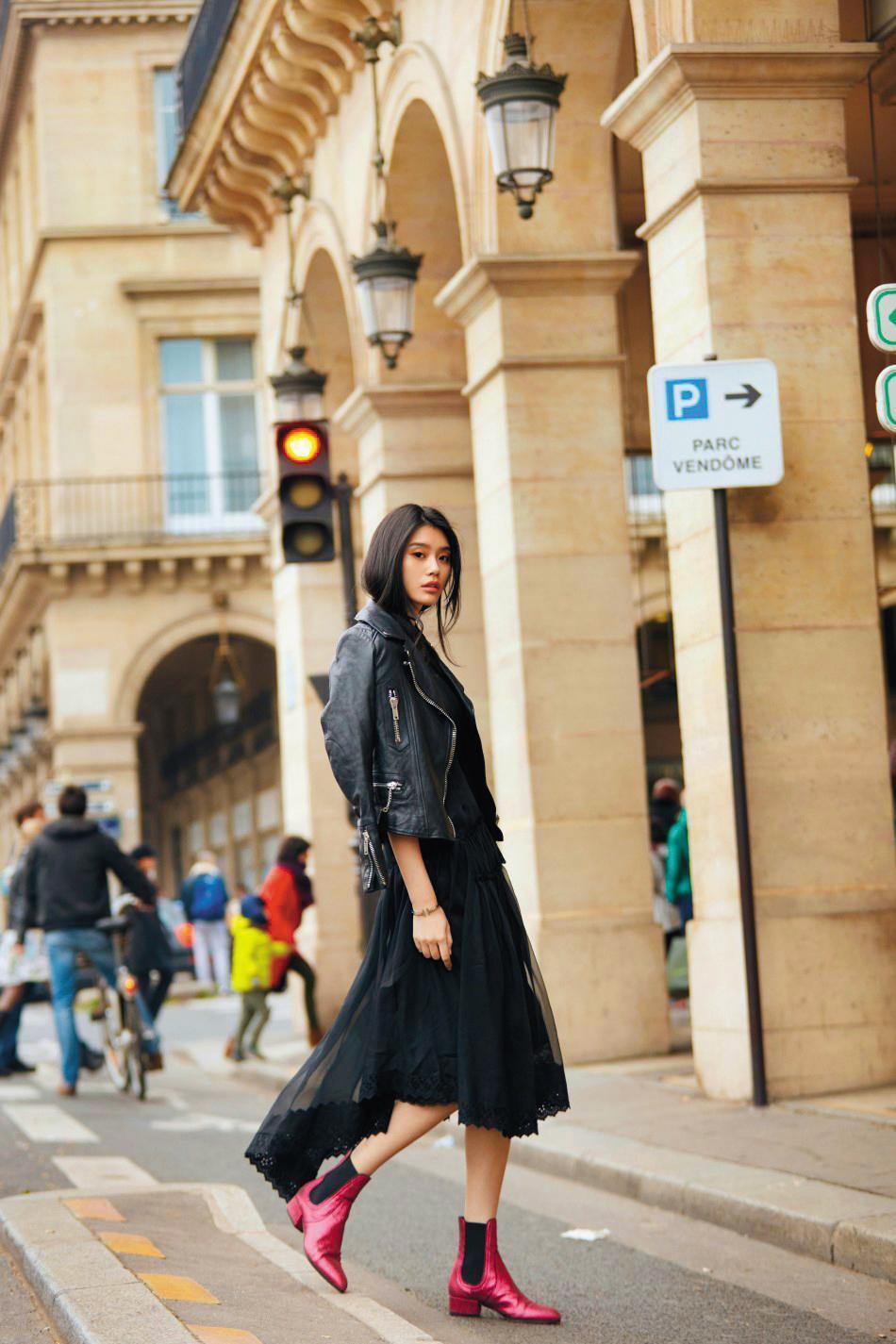 超模奚夢瑤的街拍照片,用黑色皮衣、亮面紅色短靴,搭配前短後長不規則剪裁的紗裙,不強調女人味,卻充滿濃濃的個性美,是只有超模才能詮釋出的強大氣場。(東方IC)