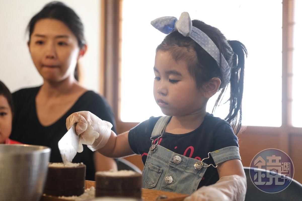 小朋友有模有樣填上鬆糕粉。