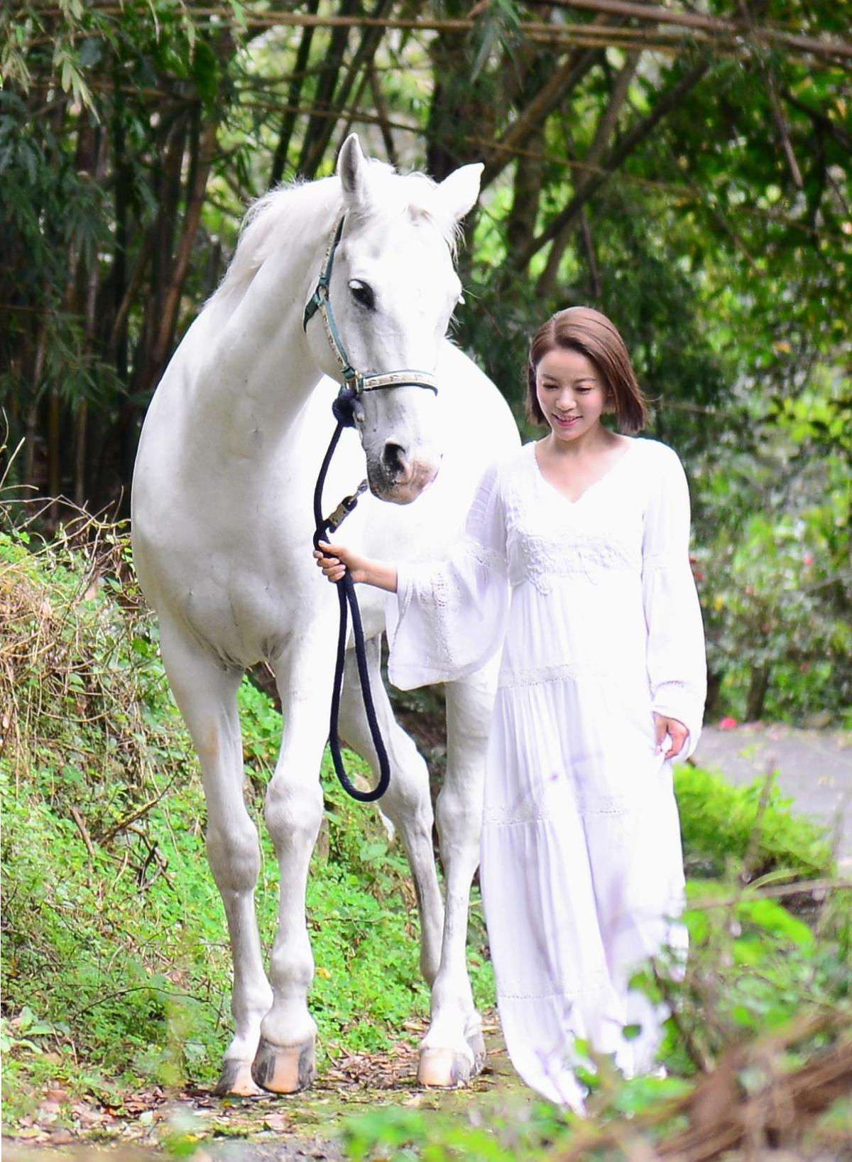 丁噹牽著不受控的白馬漫步林間,差點被他甩到山下險象環生。(相信音樂提供)