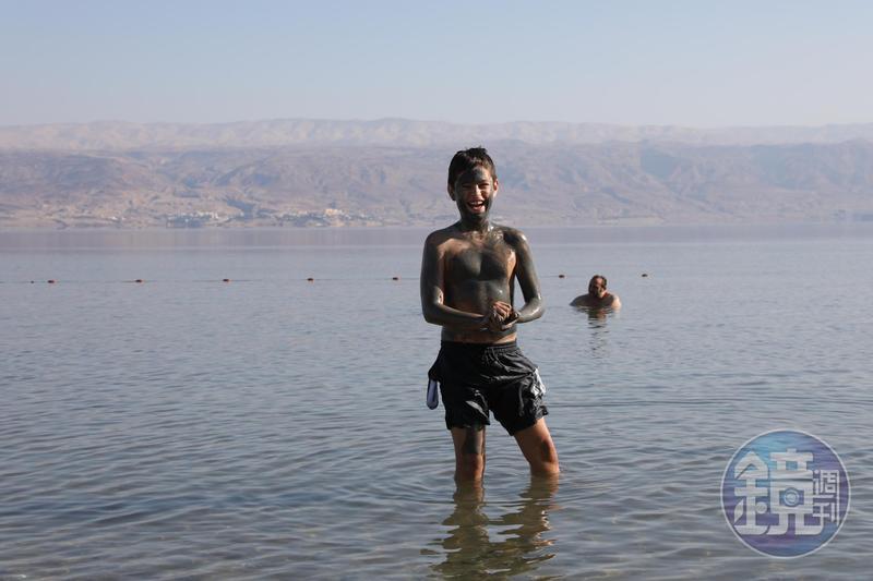 以色列男孩在自己身上塗滿死海泥,自得其樂超開心。