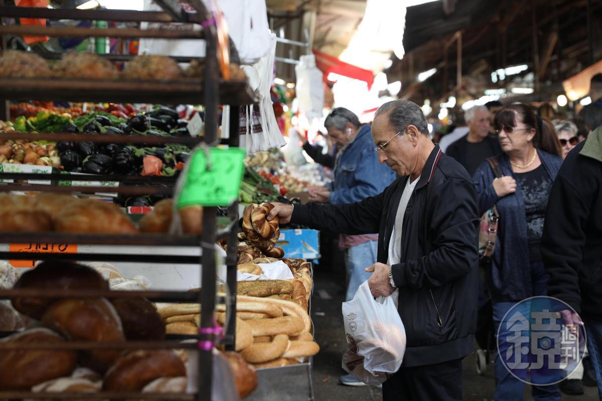 中年男子正在選購猶太麵包。