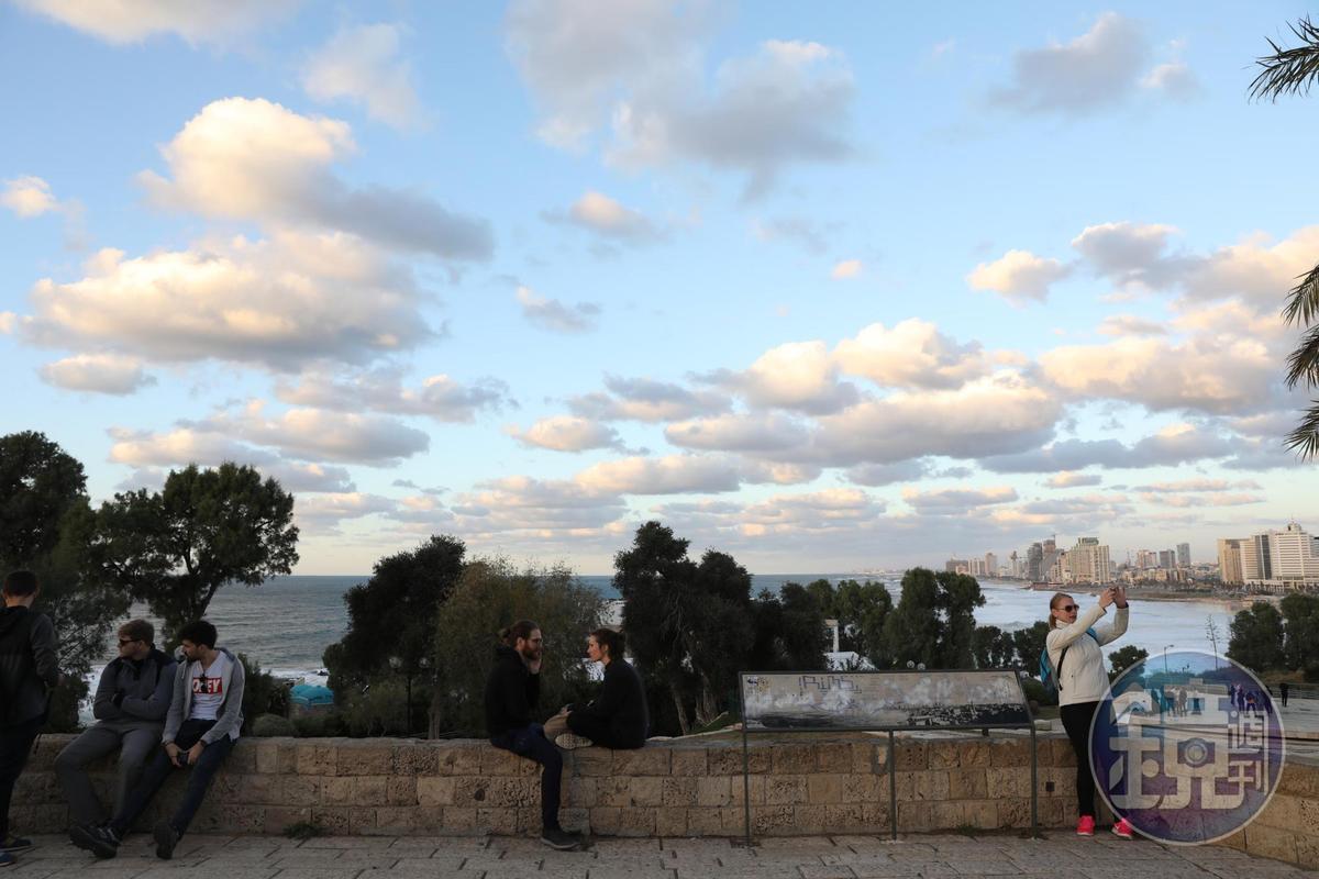 人們在雅法老城港口邊聊天自拍,狀似悠閒。
