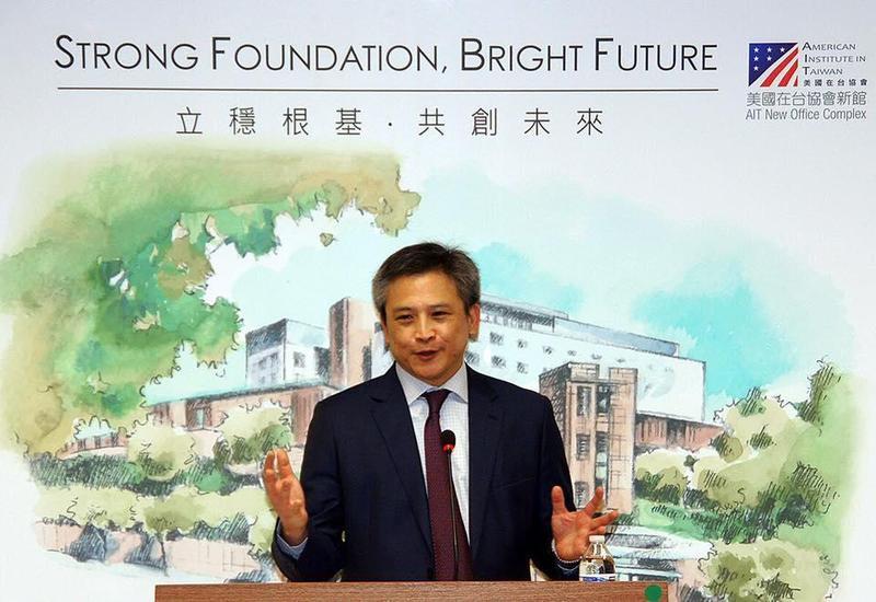美國在台協會台北辦事處處長梅健華主持AIT四十特展,背景是即將落成啟用的辦事處新館圖像。(facebook/AIT)