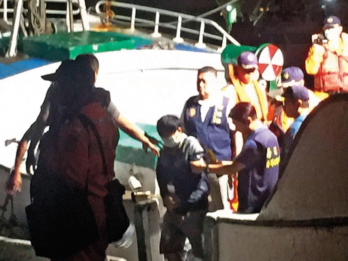 海巡隊逮捕多名越南偷渡客,並從漁船押解上岸。(翻攝畫面)