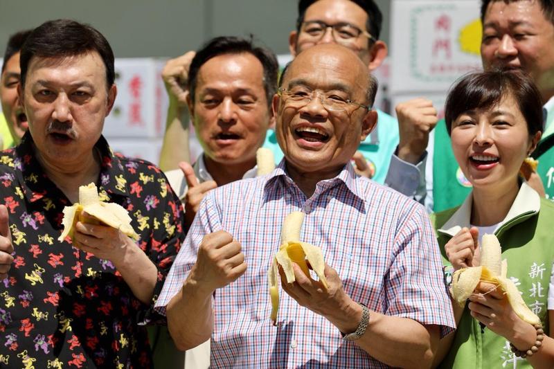 余天(左)今早出席民進黨新北市黨部香蕉推廣活動,與新北市長參選人蘇貞昌及民進黨市議員同台吃香蕉。(蘇貞昌競選辦公室提供)