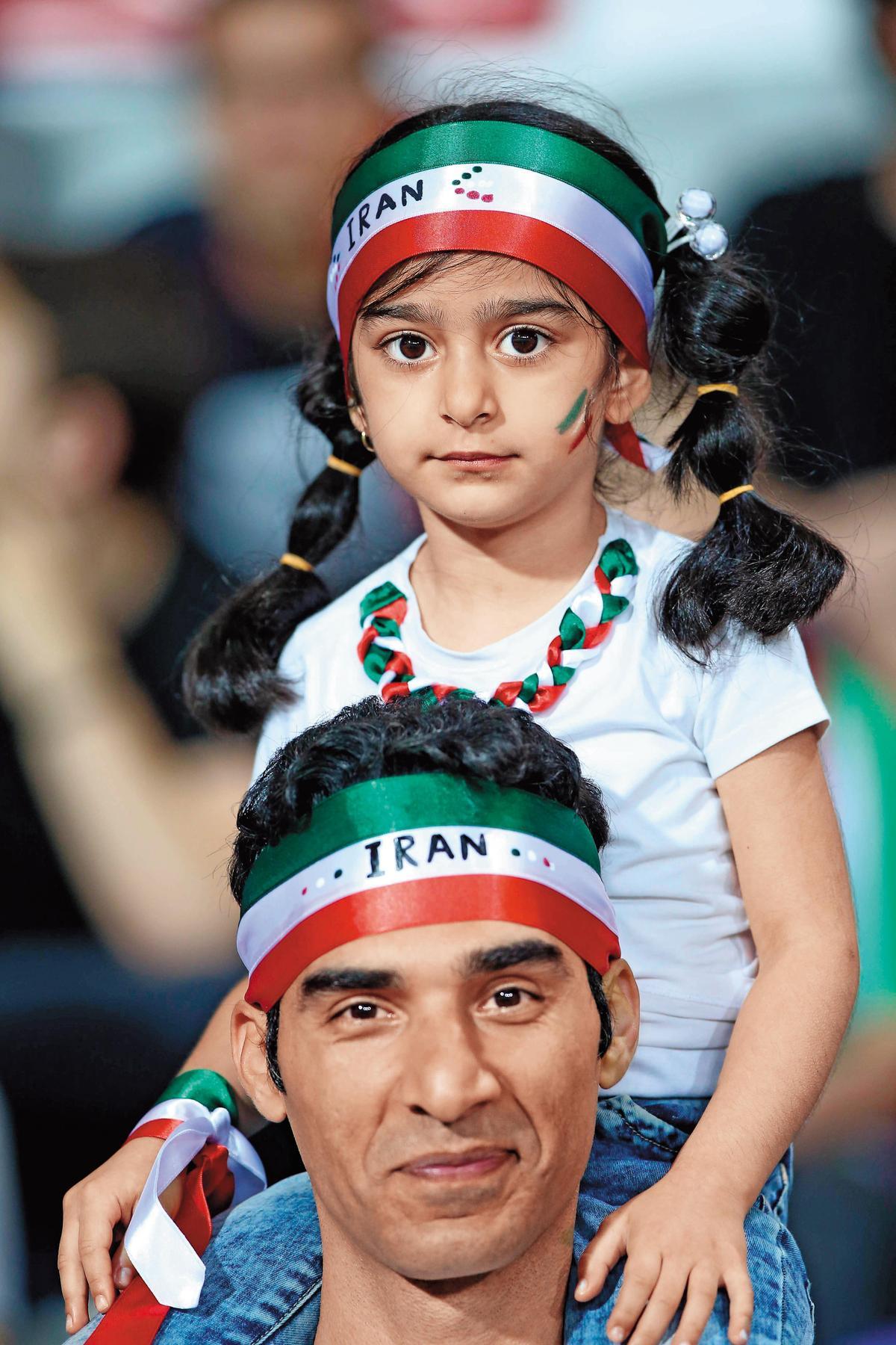 世界盃足球賽是全球最受歡迎體育盛會,熱度更勝也是四年一度的奧運賽事。圖為伊朗父女為自家球隊變裝應援。(東方IC)