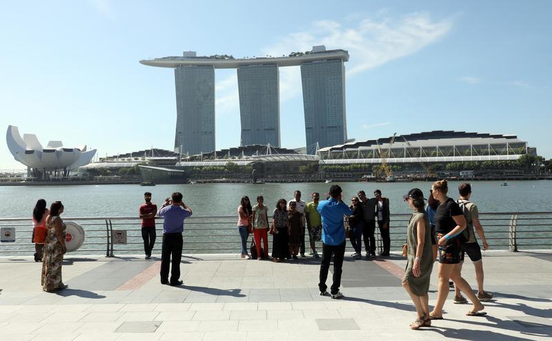 2018年6月4日,一群外國遊客在新加坡以濱海灣金沙酒店為背景拍照。(東方IC)