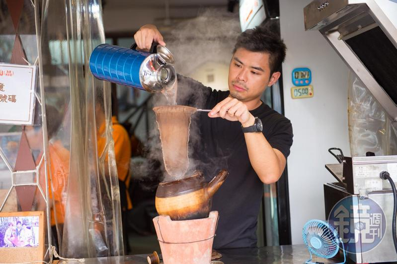 「世記咖啡」第3代主人Alvin拉起絲襪般濾布,來回冲2次滾水,咖啡香醇順口。