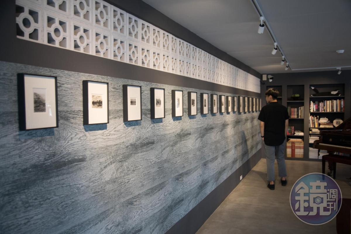 旅人佇足欣賞攝影大師郎靜山的作品。