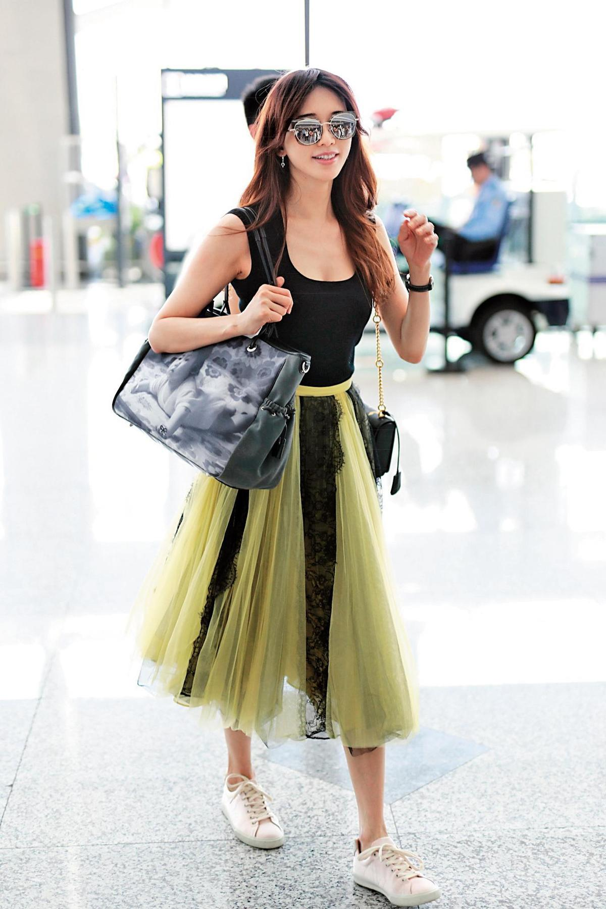 現身上海機場的林志玲,雖已是熟女年齡,不過依然保有名模身材,貼身的黑色背心下是撞色蕾絲紗裙,除了展現優雅女人味,也不忘秀出好身材的妙招。(東方IC)