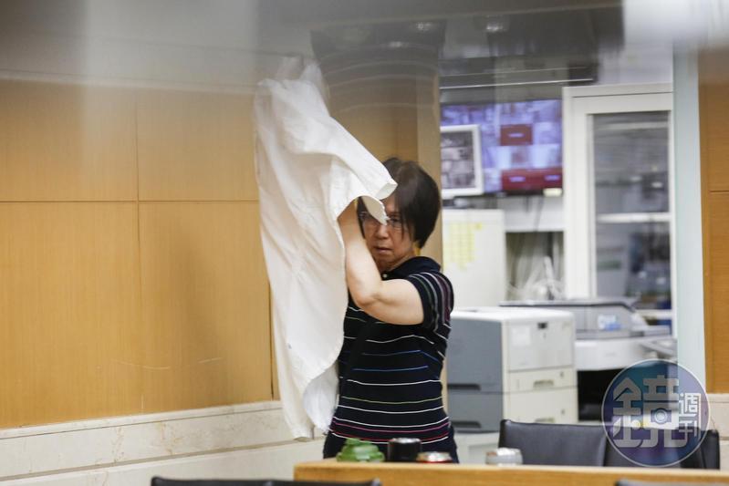 王永慶的謝姓外甥女涉炒股遭約談 ,見本刊採訪,立刻用外套遮臉。