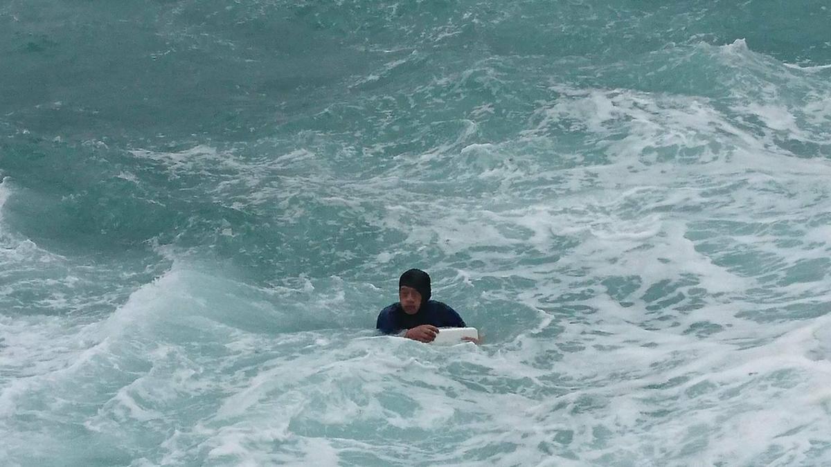 上午9時50分許,1名男性釣客不慎遭大浪捲入海裡,所幸釣客有穿救生衣,15分鐘後被民眾用救生圈拉上岸。(翻攝畫面)