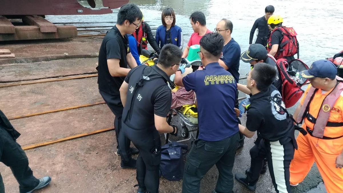 救難人員緊急將2人救起,但其中1名釣客失去生命跡象,救難人員現場為他急救。(翻攝畫面)
