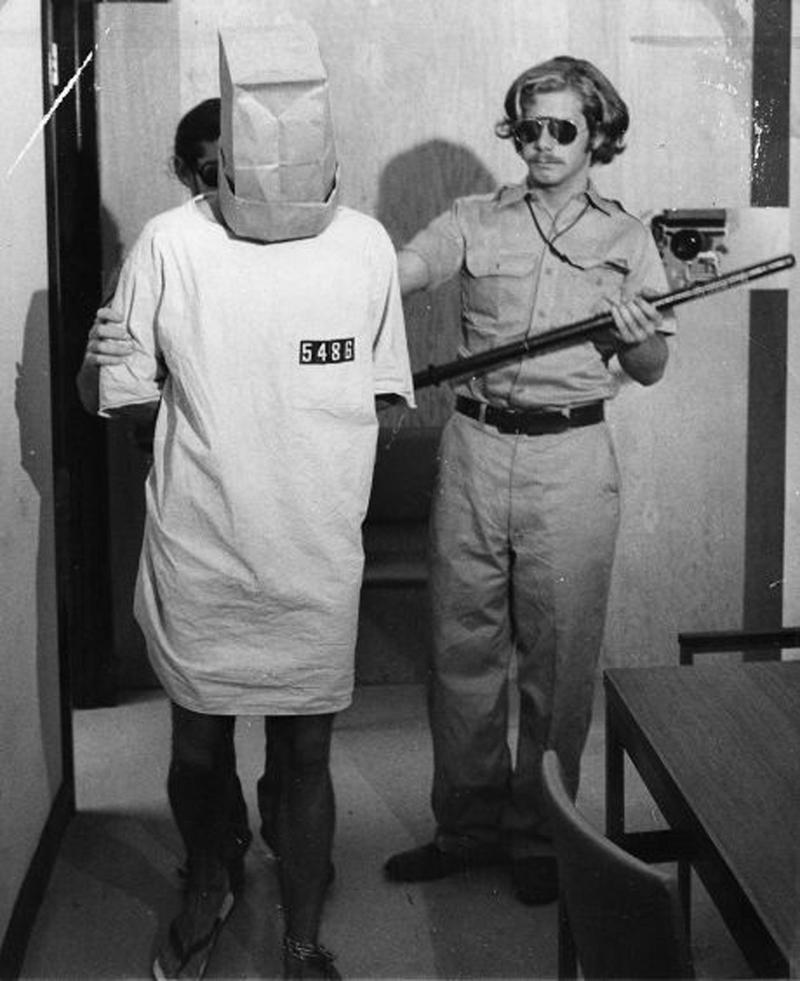1971年心理學家辛巴多主持的「史丹佛監獄實驗」。圖為實驗中擔任「獄警」的John Loftus站在被迫套上紙袋的「囚犯」後面。(東方IC)