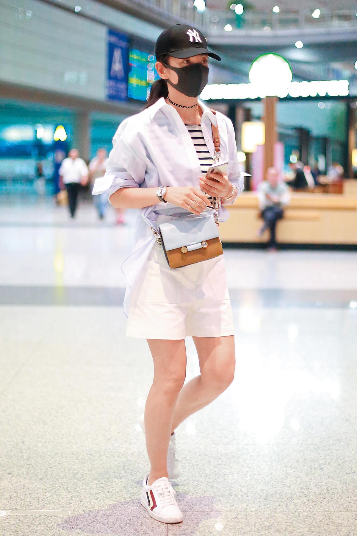 當你穿著一身白時,有個主視覺的image跳出來,反而更能凸顯;李冰冰就是在白色系的襯衫、短裙、休閒鞋中,加入條紋T-Shirt,讓整個look顯得清爽雅緻。(東方IC)