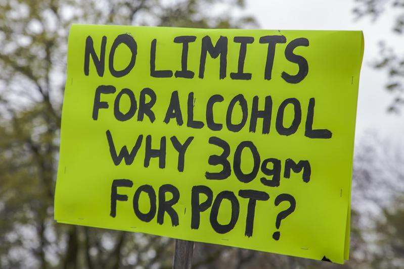 支持大麻合法的遊行民眾中,有人舉著標語質問:「酒精沒設限,為什麼30克的大麻(犯法)?」(東方IC)