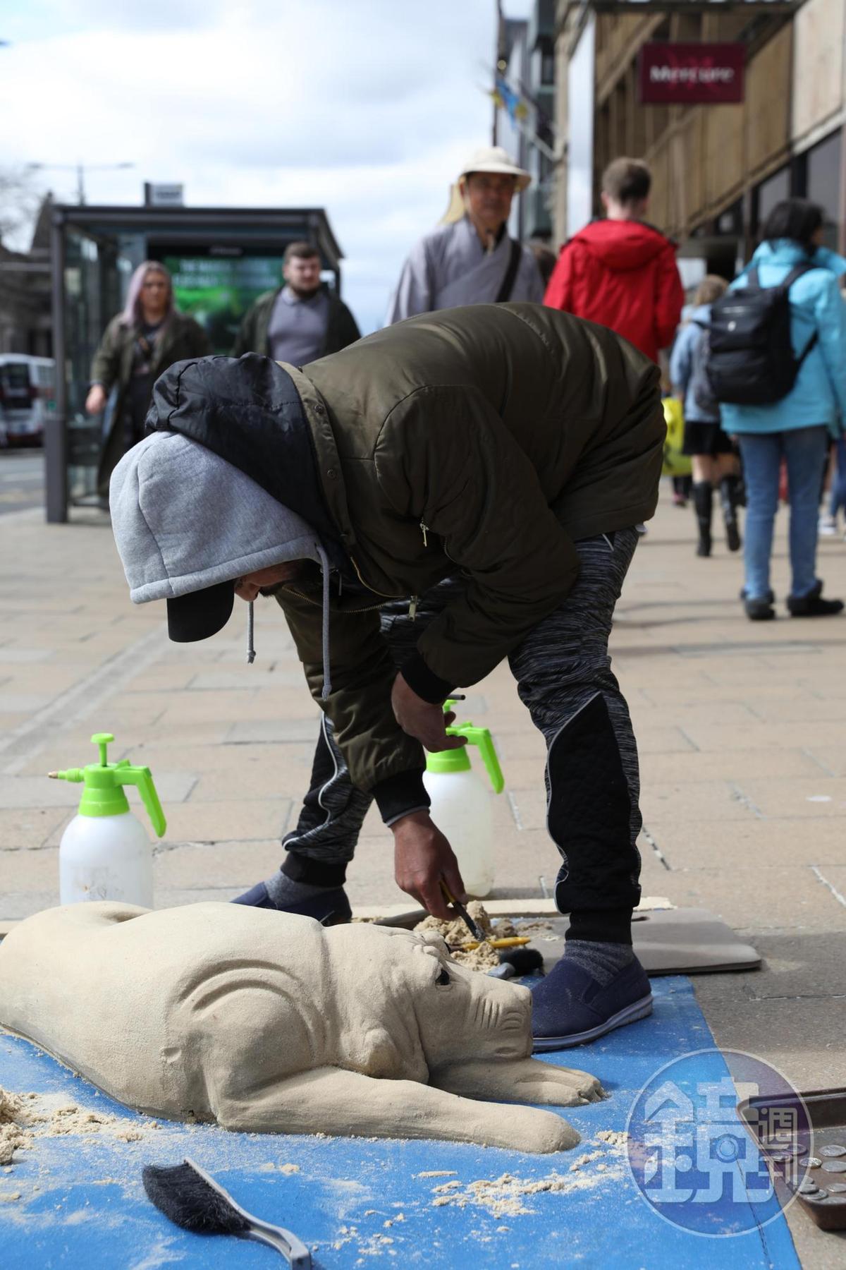 藝術家在街頭即興創作栩栩如生的沙雕狗。
