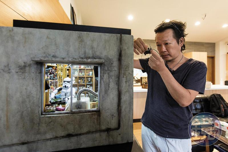 「宅男的房間」作品無實際場景參考,鄭鴻展說,平時靈感來源多來自日常生活及國外畫家的IG、臉書和插畫,他再思考把平面做成微縮模型的可能性。手上所持壓縮機為廢料製作。