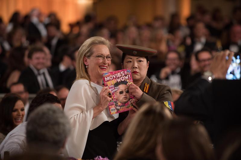2015年金球頒獎典禮上,飾演北韓記者的趙牡丹拿虛構的雜誌和梅莉史翠普合照,封面是北韓領導人金正恩。(東方IC)
