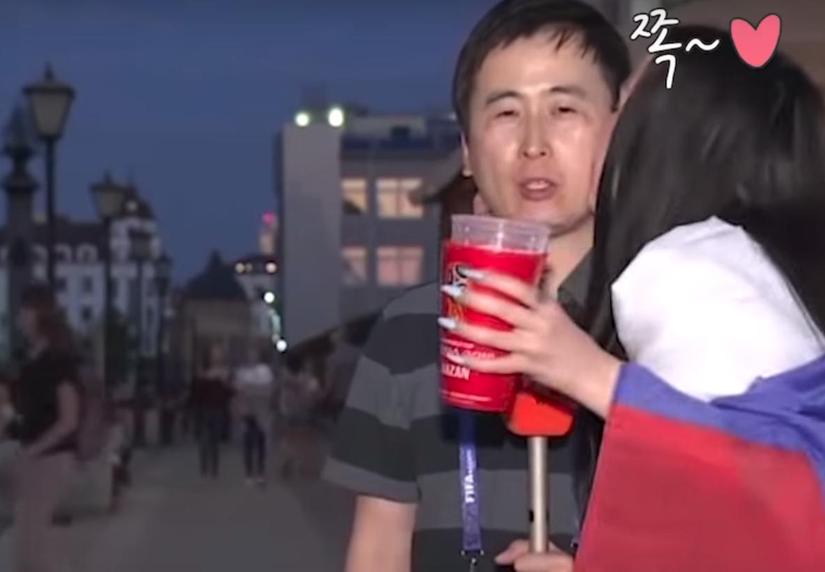 男記者與棚內進行連線中,突然遭2名俄羅斯女子接連狂吻,他假裝淡定持續報導。(翻攝自YouTube)