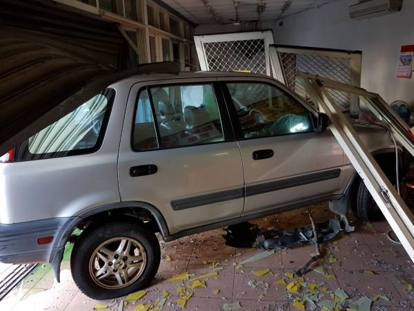 林男駕駛的休旅車卡在小吃店的鐵捲門下。(消防局提供)