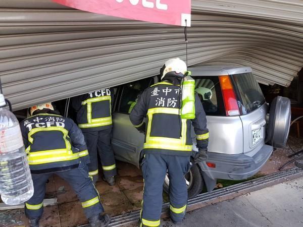 林男駕駛的休旅車衝進小吃店,消防人員趕到救援。(消防局提供)