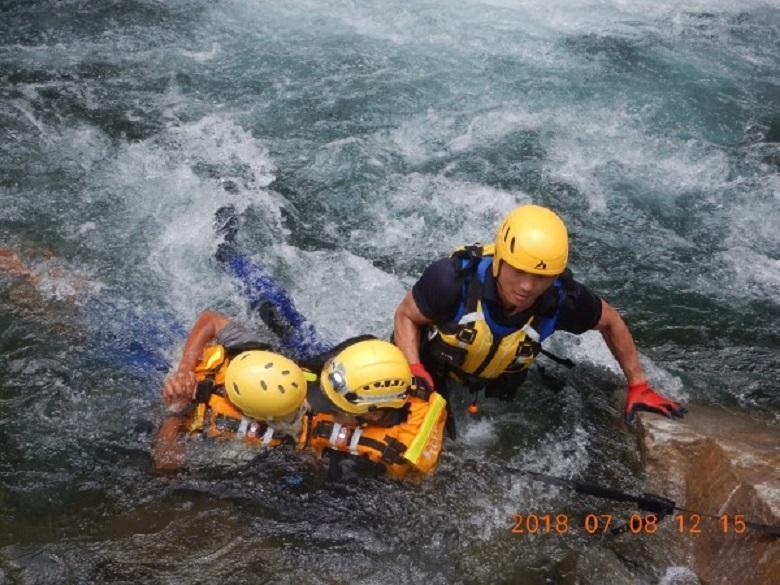 消防人員以繩索帶著嚴男渡河。(消防局提供)