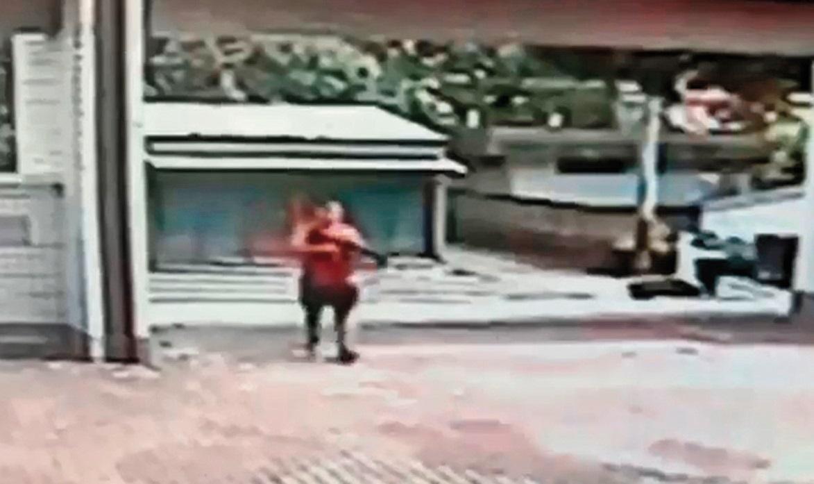 監視器畫面清楚看到江宇倫衝出校門瞄準完中輟生後,手持長槍走回校園。(翻攝畫面)