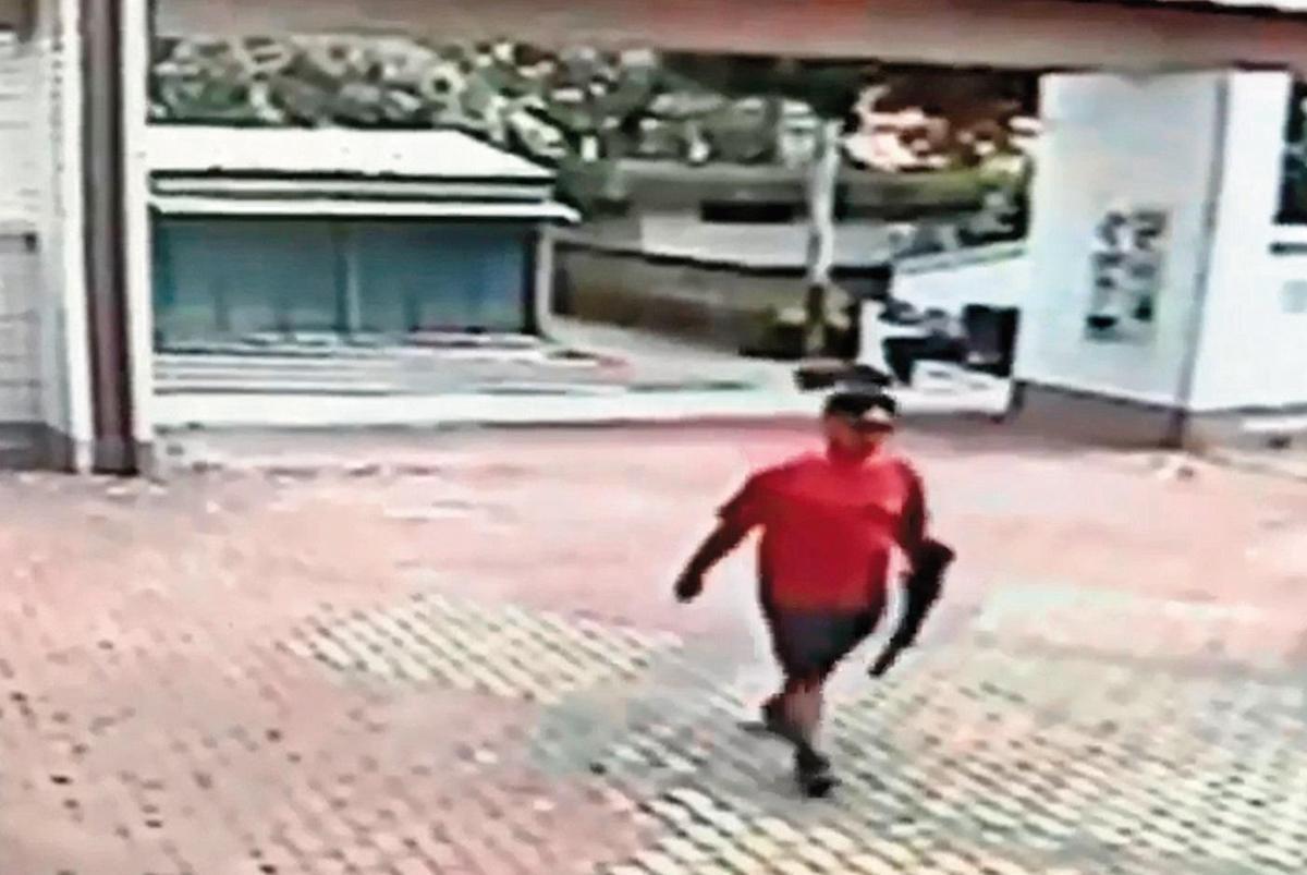 江宇倫身材壯碩被行政人員一眼認出,手上還拿著長槍,大搖大擺地從校門口走進來。(翻攝畫面)