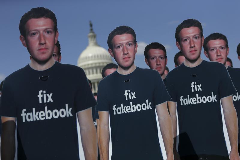 2018年4月10日祖克柏出席美國國會聽證當天,抗議人士在國會草坪擺放100個身穿「修理臉書」T恤的祖克柏人形立牌。(東方IC)