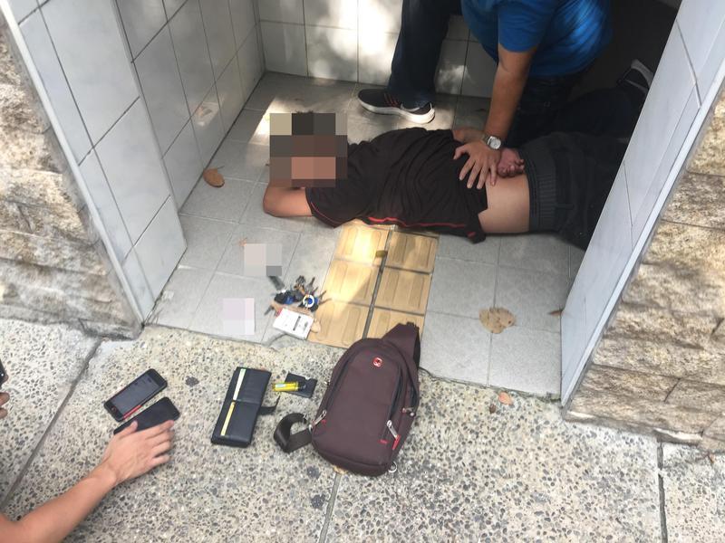 在廁所進行「死轉手」的詐騙集團成員被發現警方在他頭頂偷拍時,意圖搶奪警方手機遭警強押在地。(刑事局提供)