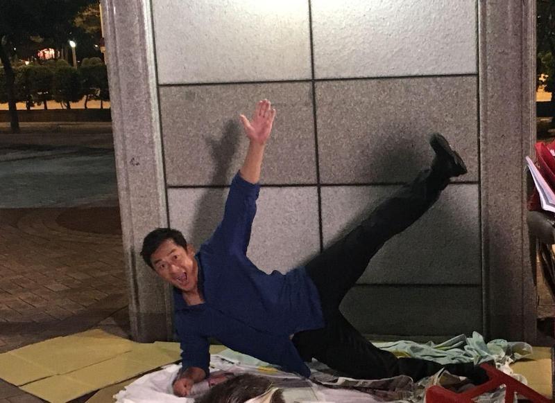 江宏恩演出流落街頭的前議員,開心的在自己的地舖上拍照。