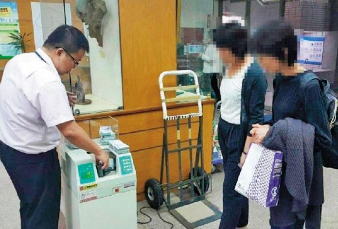日籍被害人愛子在檢警及銀行人員陪同下,逐一清點詐騙主嫌償還她的部分款項。(翻攝畫面)