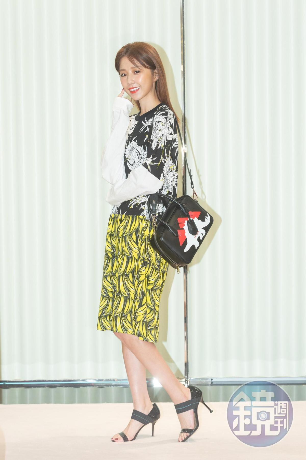 邵雨薇示範PRADA大理花拼接香蕉印花連衣裙NT$39,000、恐龍印花方包NT$67,500、運動風露趾高跟鞋NT$32,000。