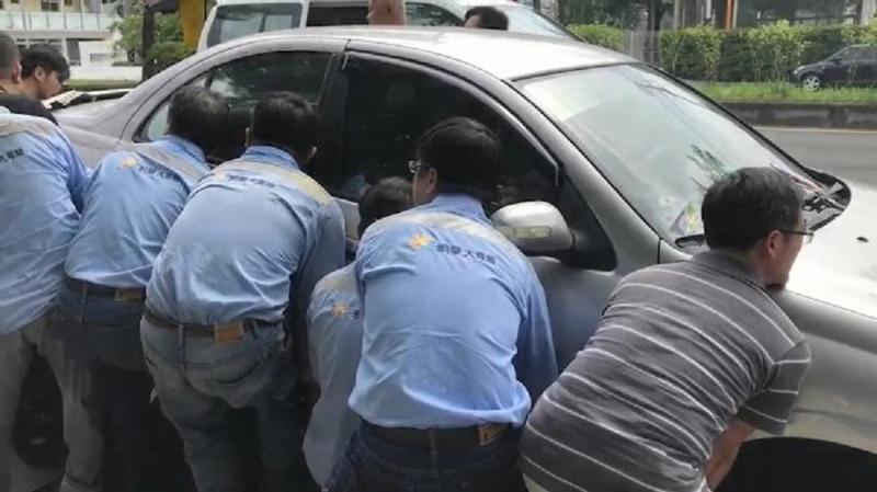 十多名壯漢在轎車兩邊合力抬車。(警方提供)