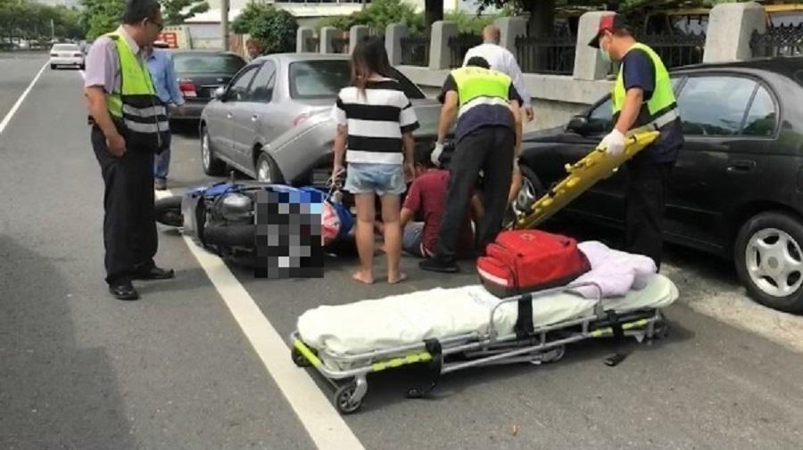 2部機車擦撞後,男騎士滑進轎車車盤底下,等待救援。(警方提供)