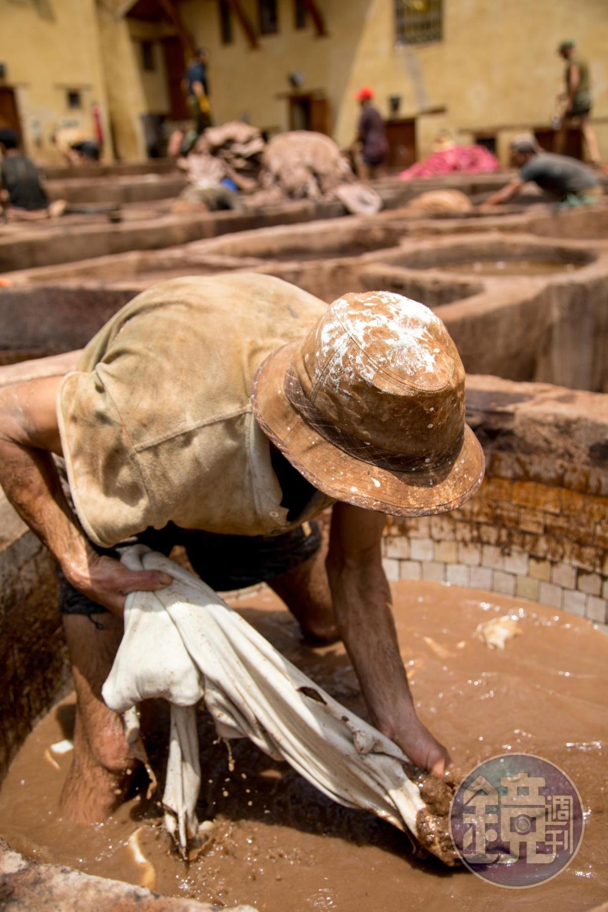 反覆搓揉後,皮才會上色,工人身上都染滿染料。